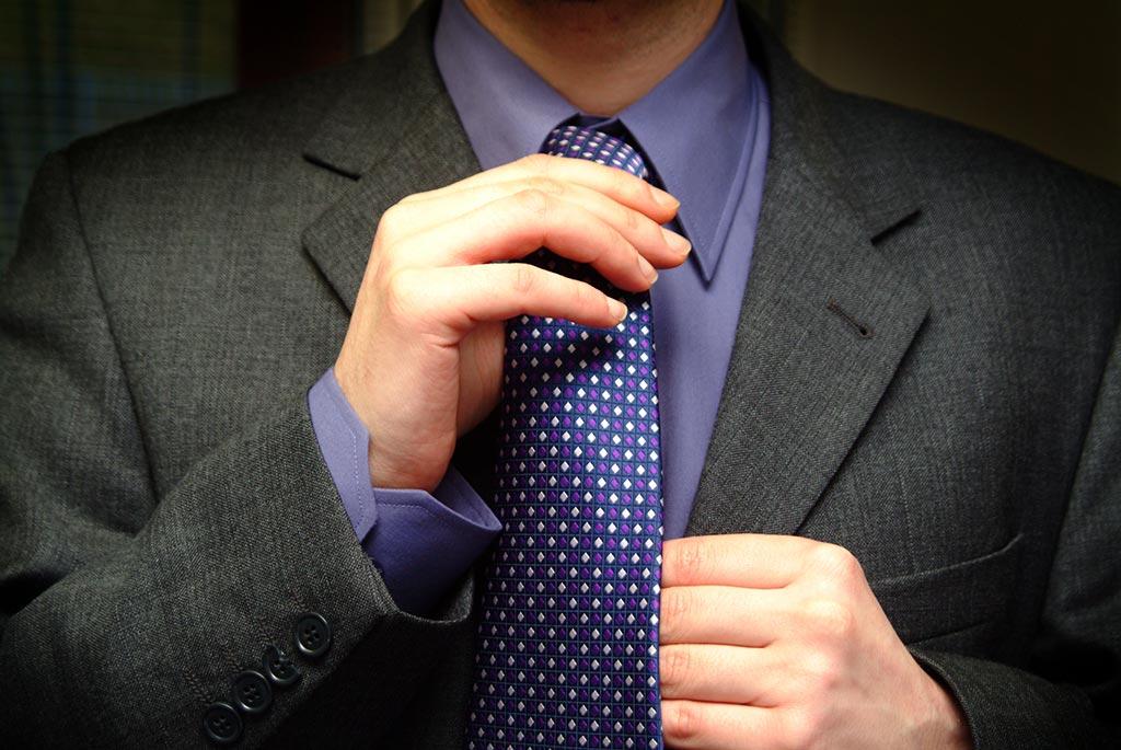 closeup of man fixing his tie